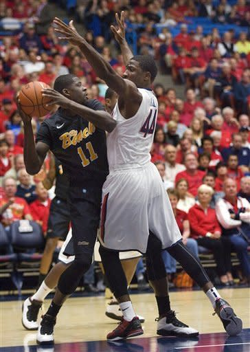 Long Beach State's James Ennis (11) looks to pass the ball around Arizona's Solomon Hill (44) during the first half of an NCAA college basketball game in Tucson, Ariz., Monday, Nov. 19, 2012. (AP Photo/Wily Low)