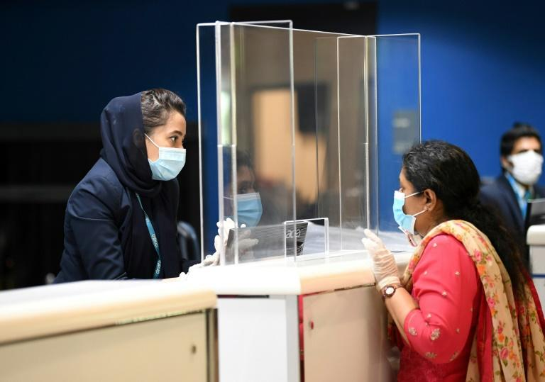 An Indian woman checks in at the Dubai International Airport before leaving the Gulf Emirate on a flight back to her country, on May 7, 2020 (AFP Photo/Karim SAHIB)
