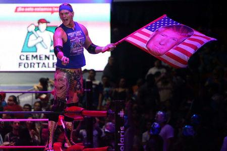 U.S. wrestler Sam Adonis, 27, role-playing as a fan of U.S. President Donald Trump, waves a flag with Trump's face during a wrestling fight at the Coliseo Arena, in Mexico City