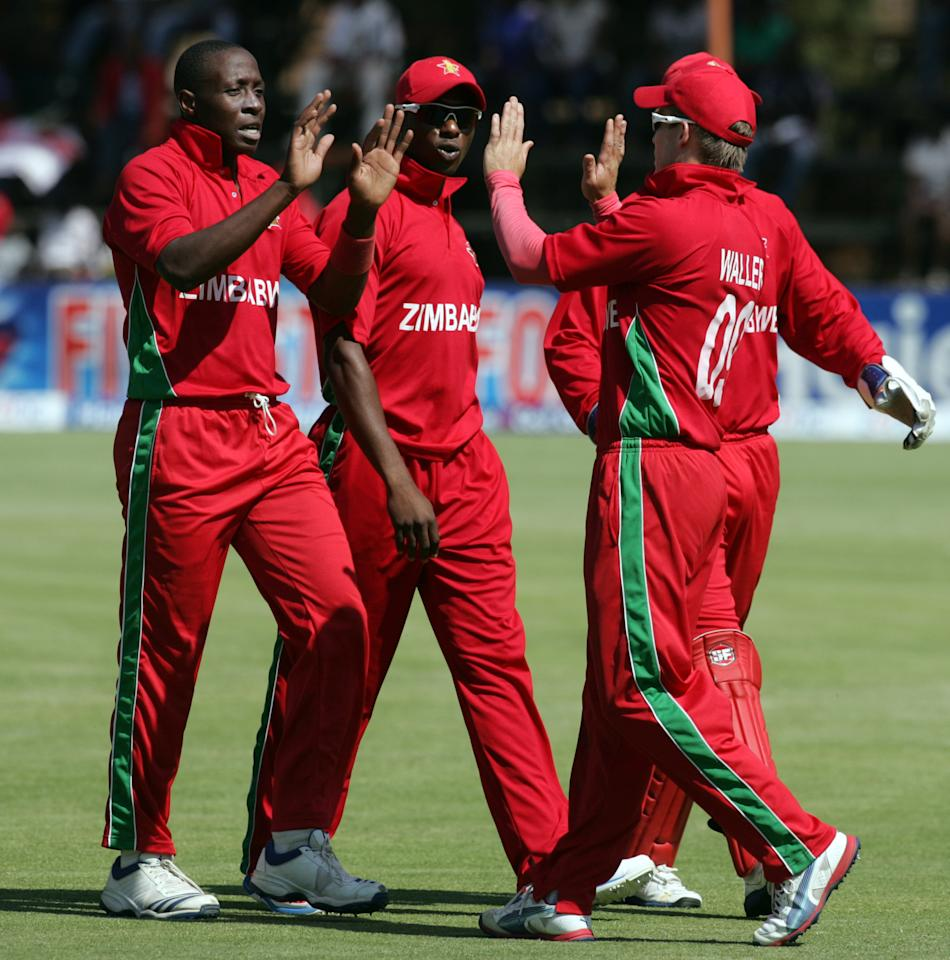 Zimbabwe players celebrate a wicket during the second game of the two match T20 cricket series between Pakistan and Zimbabwe at the Harare Sports Club on August 24, 2013.  AFP PHOTO / JEKESAI NJIKIZANA        (Photo credit should read JEKESAI NJIKIZANA/AFP/Getty Images)