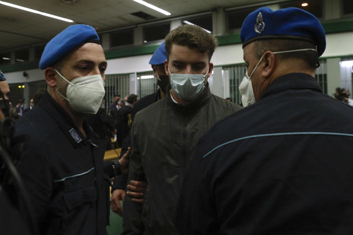 Gabriel Natale-Hjorth is escorted by police officers during the trial for the slaying of an Italian plainclothes police officer in Rome in summer 2019, in Rome, Wednesday, May 5, 2021. A jury in Rome has convicted two American friends in the 2019 slaying of a police officer in a drug sting gone awry, sentencing them to life in prison. The jury delivered more than 12 hours before delivering the verdicts late Tuesday against 21-year-old Finnegan Lee Elder and 20-year-old Gabriel Natale. (AP Photo/Gregorio Borgia)