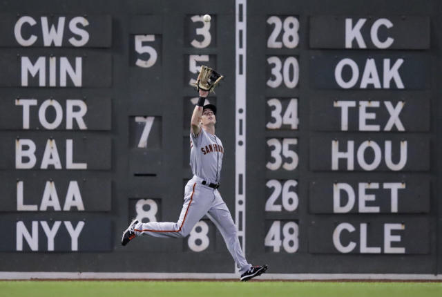 San Francisco Giants left fielder Mike Yastrzemski fields a fly out by Boston Red Sox's Andrew Benintendi during the sixth inning of a baseball game at Fenway Park in Boston, Tuesday, Sept. 17, 2019. (AP Photo/Charles Krupa)