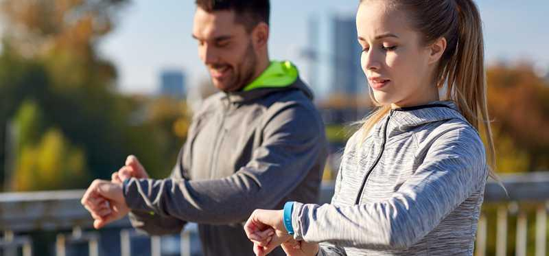 Two young people check their fitness trackers.
