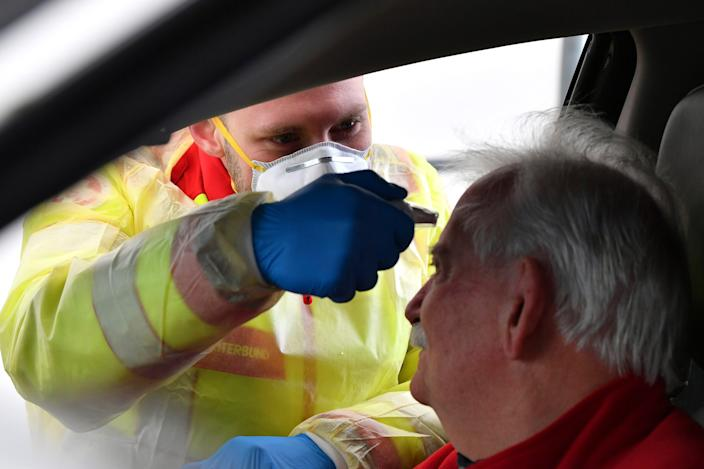 A medical staff member takes the temperature of a traveler at a border crossing between Austria and Italy on March 10, 2020.