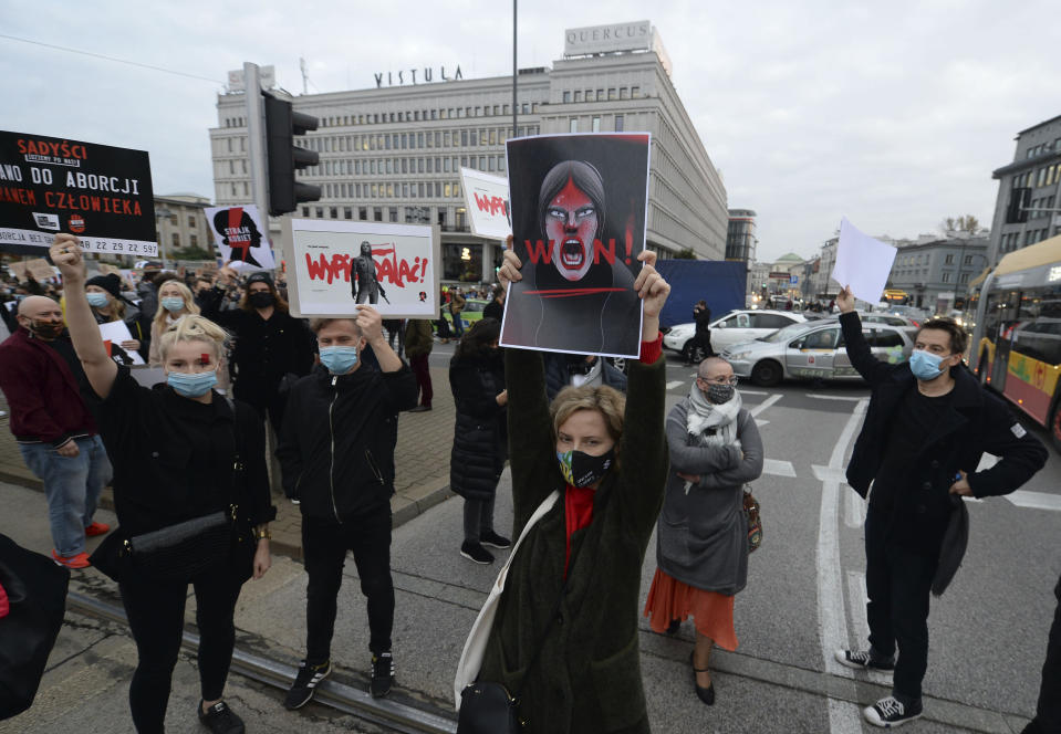 Angered protesters block rush-hour traffic at a major roundabout on the fifth day of nationwide protests against recent court ruling that tightened further Poland's restrictive abortion law, in Warsaw, Poland, on Monday, Oct. 26, 2020. The court effectively banned almost all abortions. (AP Photo/Czarek Sokolowski)