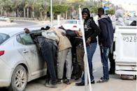 African casual labourers clamour for odds jobs from the occupant of a car in Libya's capital Tripoli