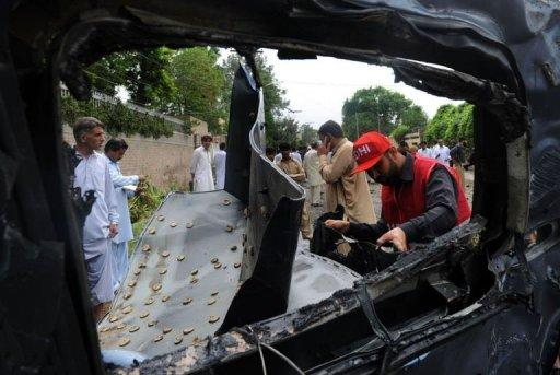 Pakistani rescuers inspect the badly damaged US consulate vehicle at a bomb blast site