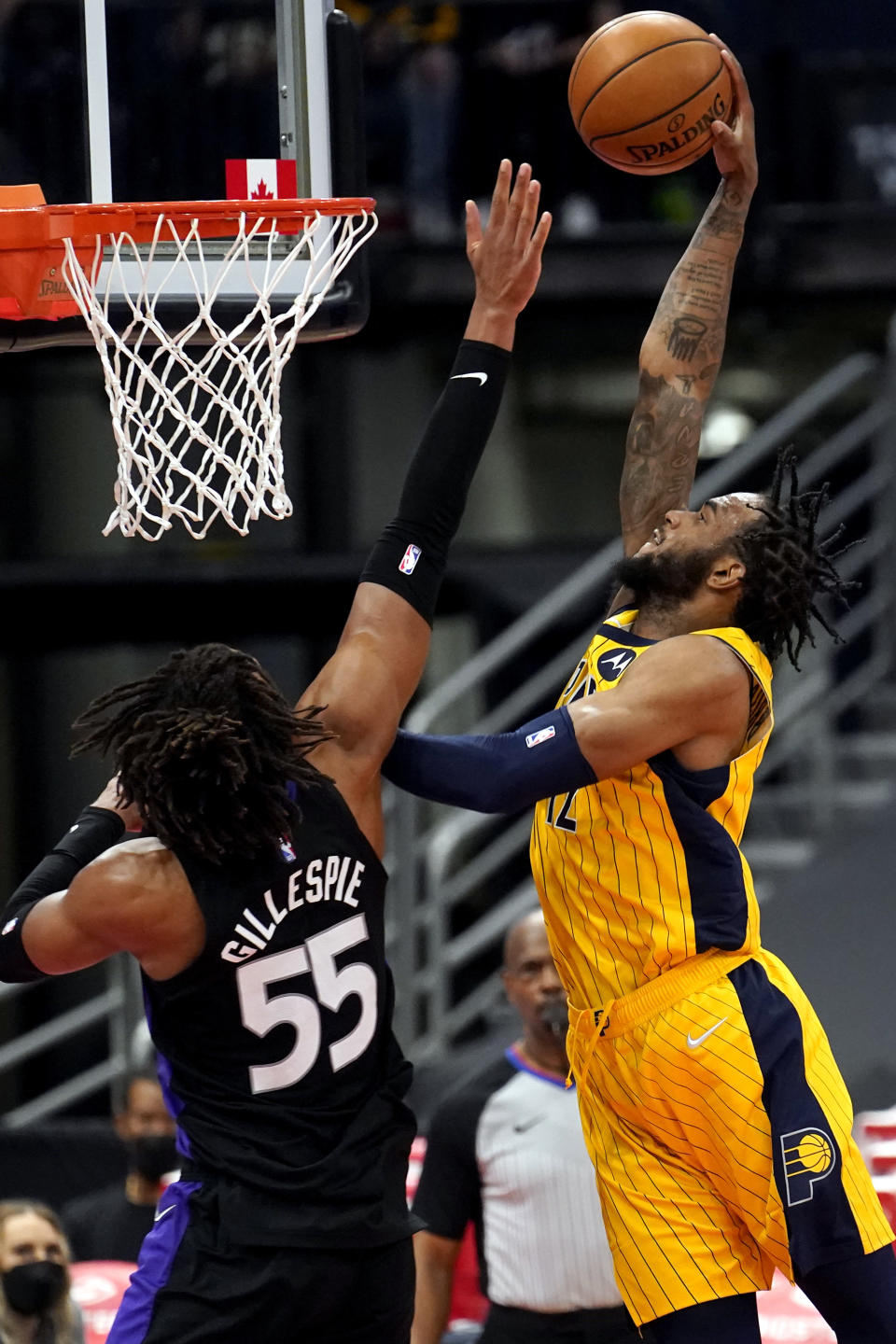 Indiana Pacers forward Oshae Brissett (12) goes up for a slam dunk in front of Toronto Raptors forward Freddie Gillespie (55) during the second half of an NBA basketball game Sunday, May 16, 2021, in Tampa, Fla. (AP Photo/Chris O'Meara)