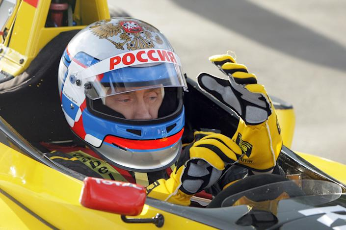 Russian Prime Minister Vladimir Putin wears a helmet and the uniform of the Renault Formula One team before driving a F1 race car on a special track in Leningrad region outside St. Petersburg on Nov. 7, 2010.