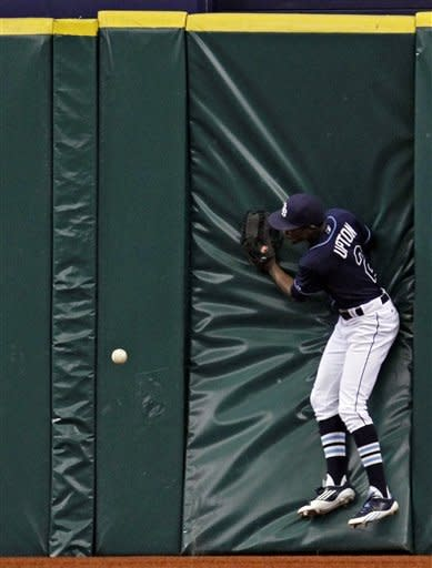 Tampa Bay Rays center fielder B.J. Upton crashes into the wall chasing a seventh-inning triple by Toronto Blue Jays' Colby Rasmus off during a baseball game, Wednesday, May 23, 2012, in St. Petersburg, Fla. (AP Photo/Chris O'Meara)