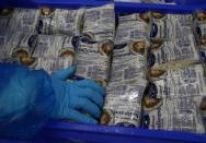 Workers pack halloumi cheese at the Petrou Bros Dairy in Aradippou