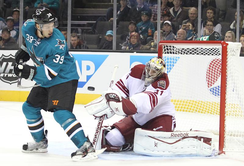 The Sharks' Logan Couture screens Coyote goalie Mike Smith during an NHL preseason hockey game in San Jose, Calif., Saturday, Sept. 21, 2013. The Sharks won 3-2 in overtime. (AP Photo/Mathew Sumner)