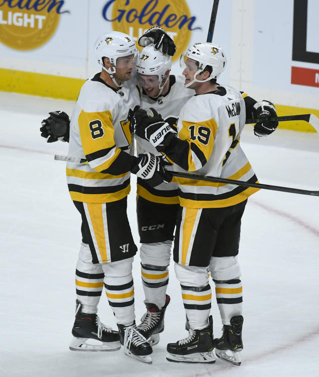 Pittsburgh Penguins center Sam Lafferty, center, celebrates with defenseman Brian Dumoulin (8) and winger Jared McCann (19) after scoring an empty-net goal during the third period of the team's NHL hockey game against the Minnesota Wild on Saturday, Oct. 12, 2019, in St. Paul, Minn. The Penguins won 7-4. (AP Photo/Craig Lassig)