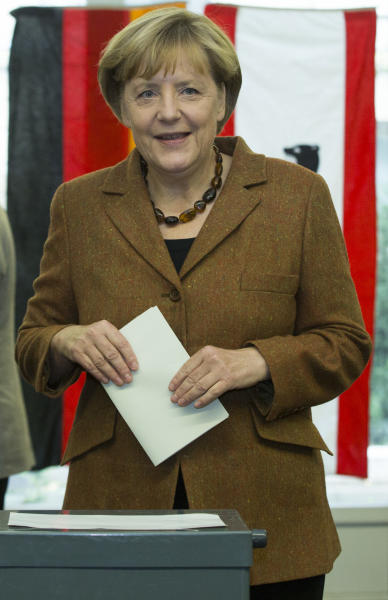 German Chancellor Angela Merkel, chairwoman of the Christian Democratic party CDU, casts her vote in Berlin, Sunday, Sept. 22, 2013. 62 million voters in Germany are entitled to elect a new parliament as Merkel runs for her third term as chancellor. (AP Photo/Markus Schreiber)
