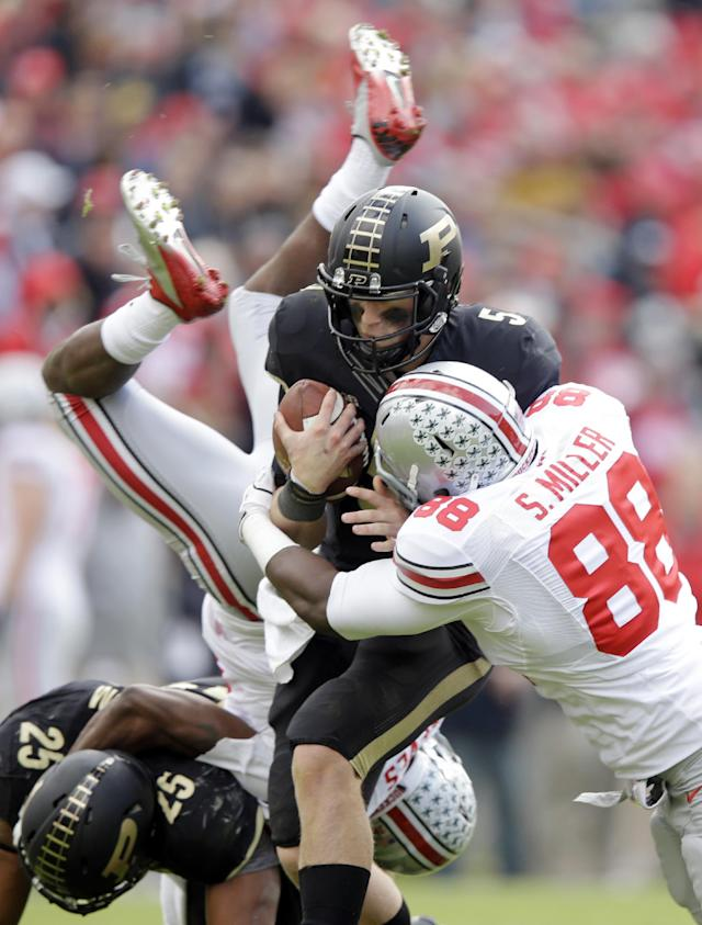 Purdue quarterback Danny Etling (50 is sacked by Ohio State defensive lineman Steve Miller (88) as Ohio State cornerback Armani Reeves flips over Purdue running back Brandon Cottom during the second half of an NCAA college football game in West Lafayette, Ind., Saturday, Nov. 2, 2013. Ohio State defeated Purdue 56-0. (AP Photo/Michael Conroy)