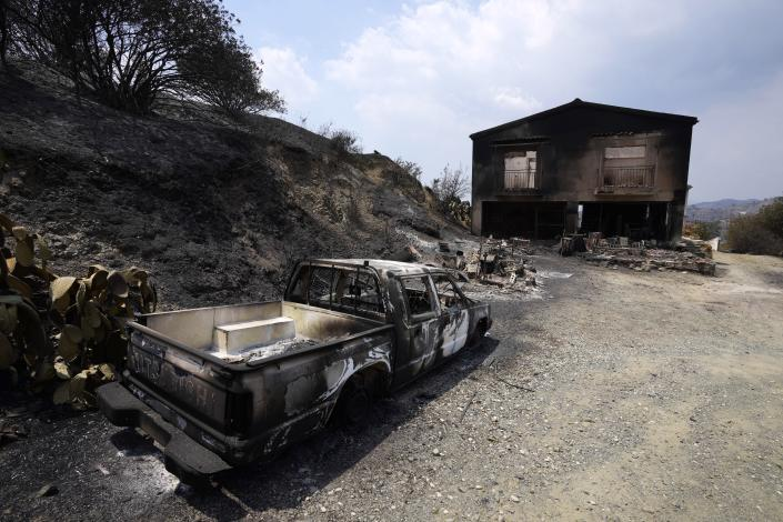 """A burned car is seen outside a damaged house on Troodos mountain, in Ora village, southwestern Cyprus, Sunday, July 4, 2021. Cyprus search crews discovered the bodies of four people outside a fire-swept mountain village on Sunday in what a government minister called the """"most destructive"""" blaze in the east Mediterranean island nation's history. (AP Photo/Petros Karadjias)"""