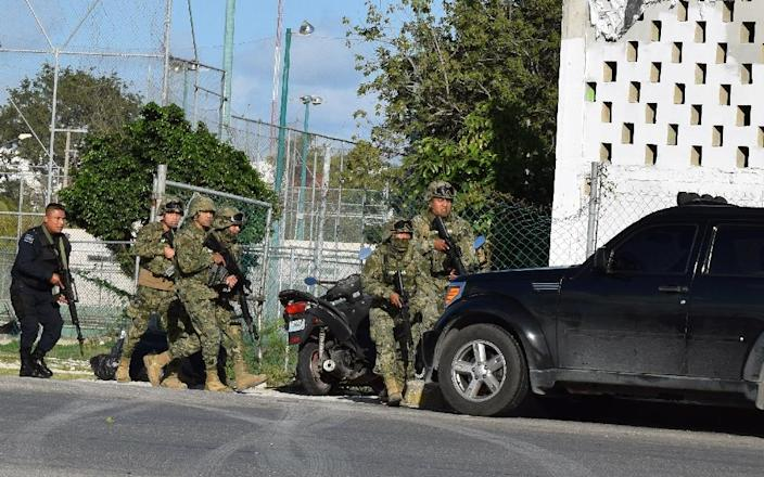 Police and soldiers take cover during an attack by gunmen on the Quintana Roo state prosecutor's office in Cancun, Mexico, which left four people dead (AFP Photo/ERICK GRAJALES)