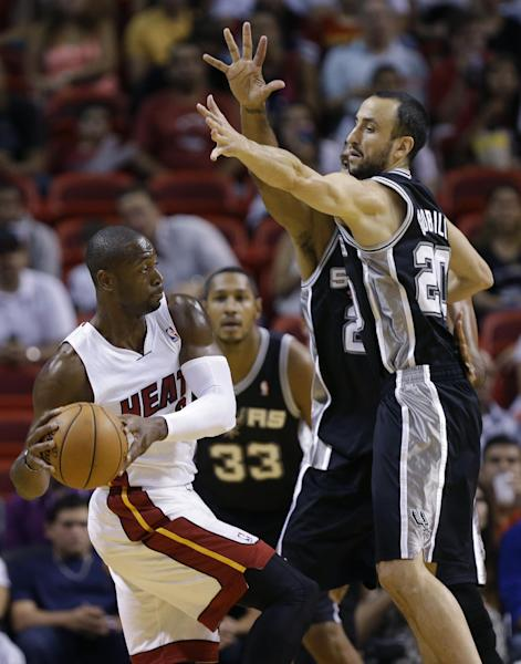 Miami Heat's Dwyane Wade (3) looks to pass as San Antonio Spurs' Manu Ginobili (20) defends during the first half of an NBA preseason basketball game, Saturday, Oct. 19, 2013, in Miami. (AP Photo/Lynne Sladky)