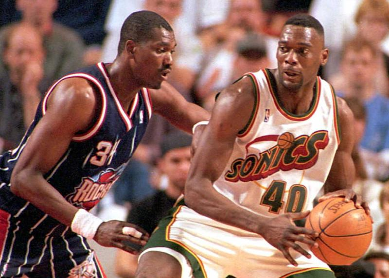 SEATTLE, WA - MAY 5: Seattle SuperSonics' Shawn Kemp tries pass Houston Rockets' Hakeem Olajuwon during their Western Conference semi-final series game on 04 May in Seattle. Kemp finished with 17 points and 12 rebounds, while Olajuwon was held to only 6 points and 4 rebounds. The SuperSonics won 108-75. (Photo credit should read Pete LEVINE/AFP via Getty Images)