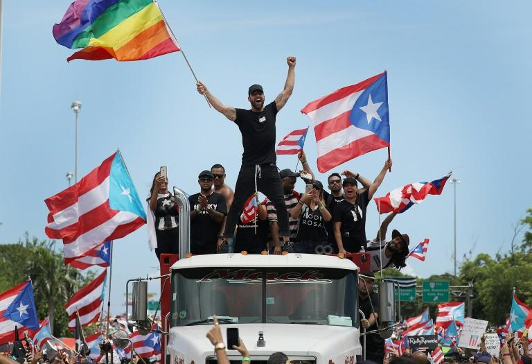Singer Ricky Martin waves a Gay Pride flag as he joins hundreds of thousands of others calling for the resignation of Puerto Rico's governor (AFP Photo/JOE RAEDLE)