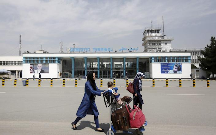 FILE PHOTO: Afghan passengers walk in front of Hamid Karzai International Airport in Kabul, Afghanistan March 29, 2016. REUTERS/Omar Sobhani/File Photo
