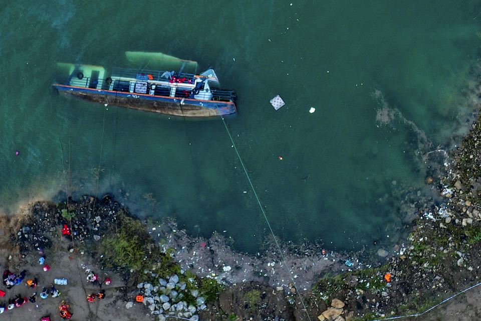 In this photo released by Xinhua News Agency, rescuers work at the site of an overturned passenger ship in Liupanshui in southwest China's Guizhou province, Sunday, Sept. 19, 2021. The boat has left multiple people dead, with several others still missing, according to state media on Sunday. CCTV said that the ship overturned shortly after it departed Saturday evening. Preliminary investigations suggest that the ship was blown over by strong winds. (Ou Dongqu/Xinhua via AP)