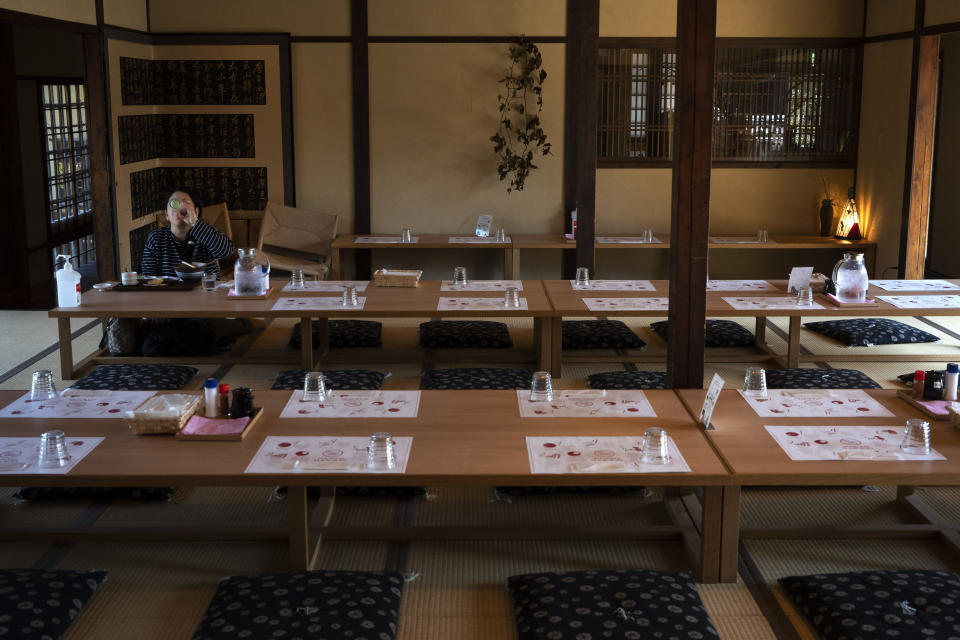 A tourist eat her lunch in a restaurant in Nara, Japan, March 19, 2020. Nara was among the first Japanese town hit by the COVID-19 in late January, when a tour bus driver in town tested positive for the virus, becoming the first Japanese patient after carrying tourists from Wuhan, the epicenter of the pandemic. (AP Photo/Jae C. Hong)