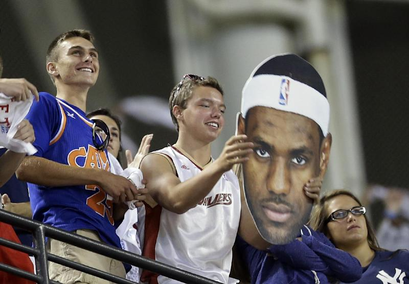 A Cleveland Cavaliers fan holds up a LeBron James poster at the New York Yankees vs Cleveland Indians baseball game Thursday, July 10, 2014, in Cleveland. (AP Photo/Tony Dejak)