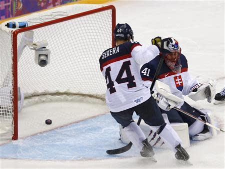 Slovakia's goalie Halak and teammate Sekera let in a goal by Slovenia's Ticar during the third period of their men's preliminary round ice hockey game at the 2014 Sochi Winter Olympic Games