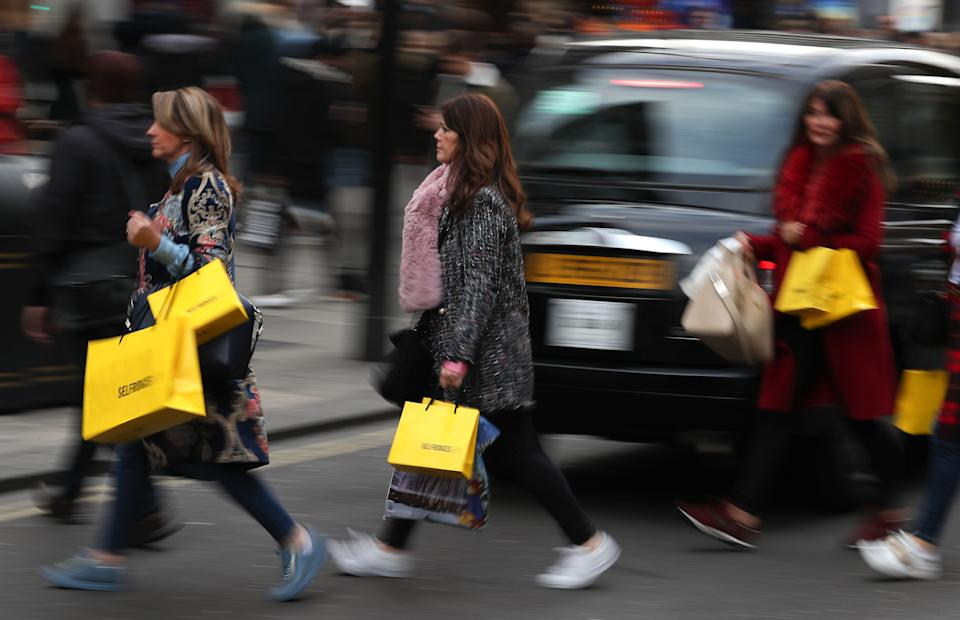 Shoppers carry their purchases in Selfridges branded bags as they cross Oxford Street in London, on November 24, 2017. Black Friday is a sales offer originating from the US where retailers slash prices on the day after the Thanksgiving holiday. In the UK it is used as a marketing device to entice Christmas shoppers with the discounts at stores often lasting for a week. / AFP PHOTO / Daniel LEAL-OLIVAS        (Photo credit should read DANIEL LEAL-OLIVAS/AFP via Getty Images)