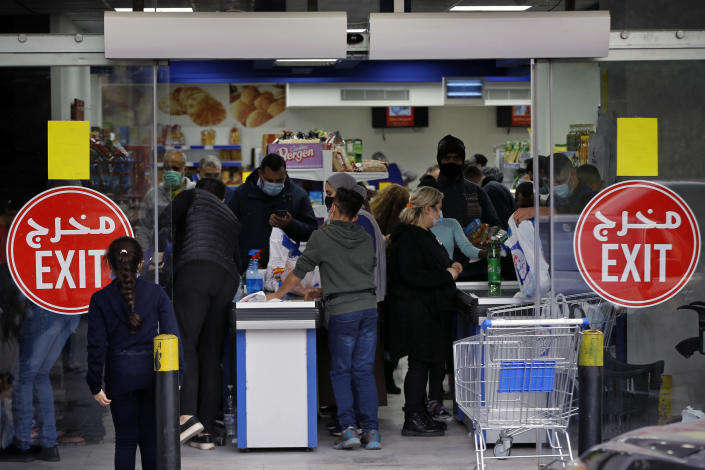 People shop at a supermarket as they begin to stock up on provisions, in Beirut, Lebanon, Monday, Jan. 11, 2021. Panic buyers swarmed supermarkets after reports the government planned to also order them shut in the tightened lockdown. Long lines formed outside chain supermarkets, sparking fear the crowds could further spread the virus. (AP Photo/Bilal Hussein)
