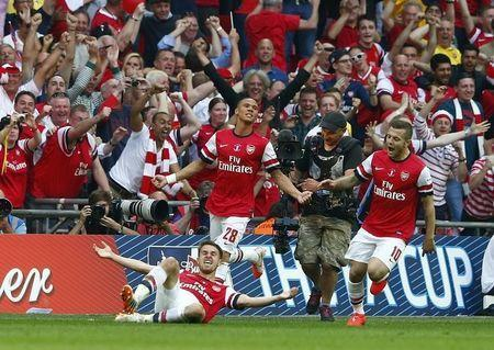 Arsenal's Aaron Ramsey (L) celebrates with team mates Kieran Gibbs (C) and Jack Wilshere after scoring his team's third goal during their FA Cup final match against Hull City at Wembley Stadium in London, May 17, 2014. REUTERS/Eddie Keogh