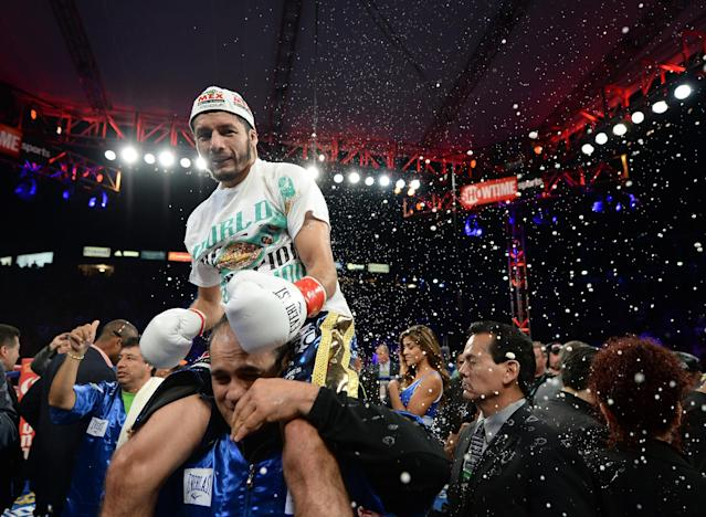 CARSON, CA - AUGUST 24: Jhonny Gonzalez ducks a thrown beer from the crowd as he celebrates his first round knockout of Abner Mares during the WBC Featherweight Title Fight at the StubHub Center on August 24, 2013 in Carson, California. (Photo by Harry How/Getty Images)