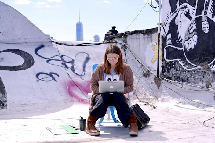 A teacher from Yung Wing School P.S. 124 who wished not be identified remote teaches on her laptop from her roof on March 24, 2020 in New York City. (Photo by Michael Loccisano/Getty Images)