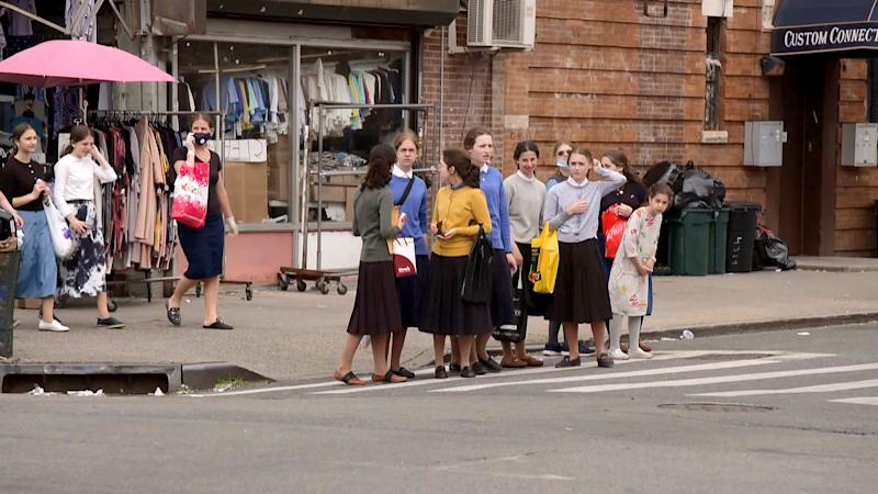 A crowd of girls gather at a crosswalk in the Borough Park neighborhood of Brooklyn, N.Y., which was hit by the virus early on. (NBC News)