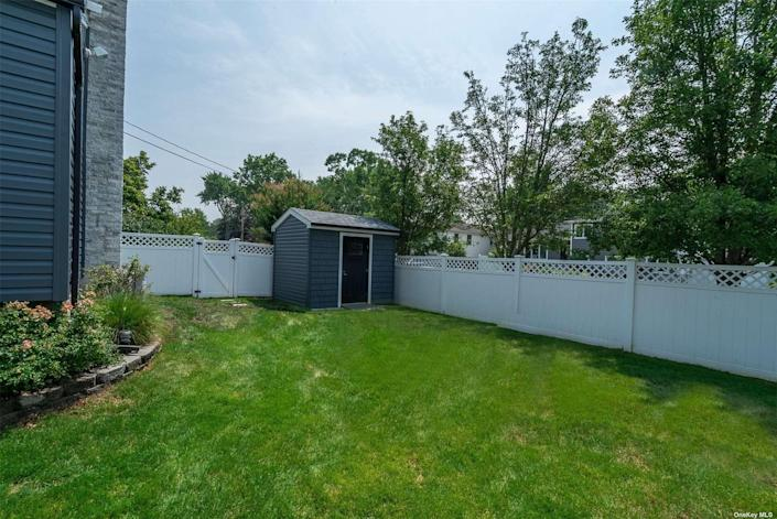 The backyard of a house on long island with grass and a small shed