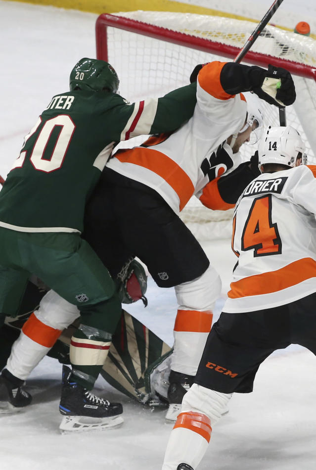 Philadelphia Flyers' James van Riemsdyk, right, is shoved by Minnesota Wild's Ryan Suter as he scores the go-ahead goal in the third period of an NHL hockey game, Tuesday, Feb. 12, 2019, in St. Paul, Minn. The Flyers won 5-4. (AP Photo/Jim Mone)