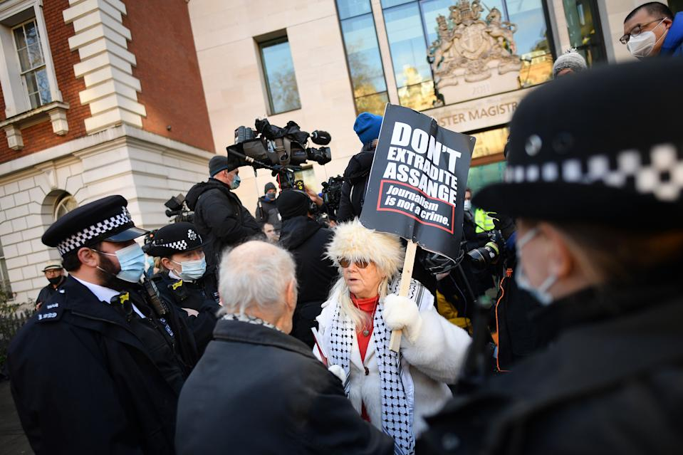 Police speak to a supporter of Wikileaks founder Julian Assange outside Westminster Magistrates court in London as he appears for a bail hearing on January 6, 2021. (Photo by JUSTIN TALLIS / AFP) (Photo by JUSTIN TALLIS/AFP via Getty Images)