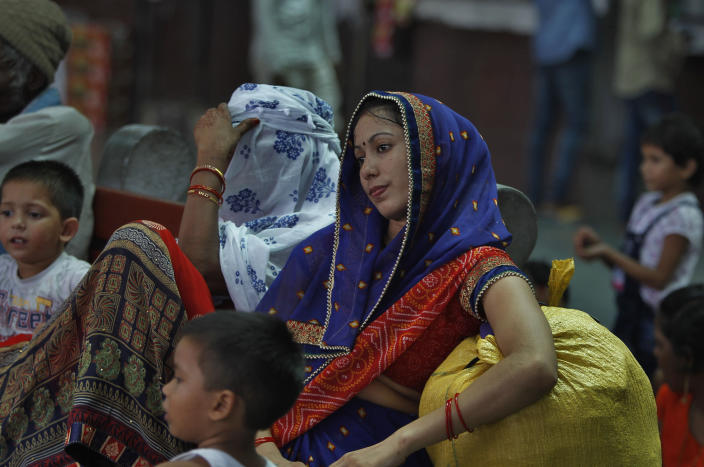 """Women tourists with their children wait for train at a railway station in Jammu, India, Sunday, Aug. 4, 2019. Thousands of Indian students and visitors were fleeing Indian-controlled Kashmir over the weekend after the government ordered tourists and Hindu pilgrims visiting a Himalayan cave shrine """"to curtail their stay"""" in the disputed territory, citing security concerns. (AP Photo/Channi Anand)"""