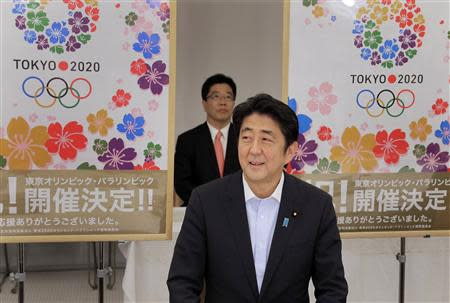 Japan's Prime Minister Abe smiles as he reports to his cabinet members Tokyo's successful bid to host the 2020 Summer Olympics and Paralympics in Tokyo