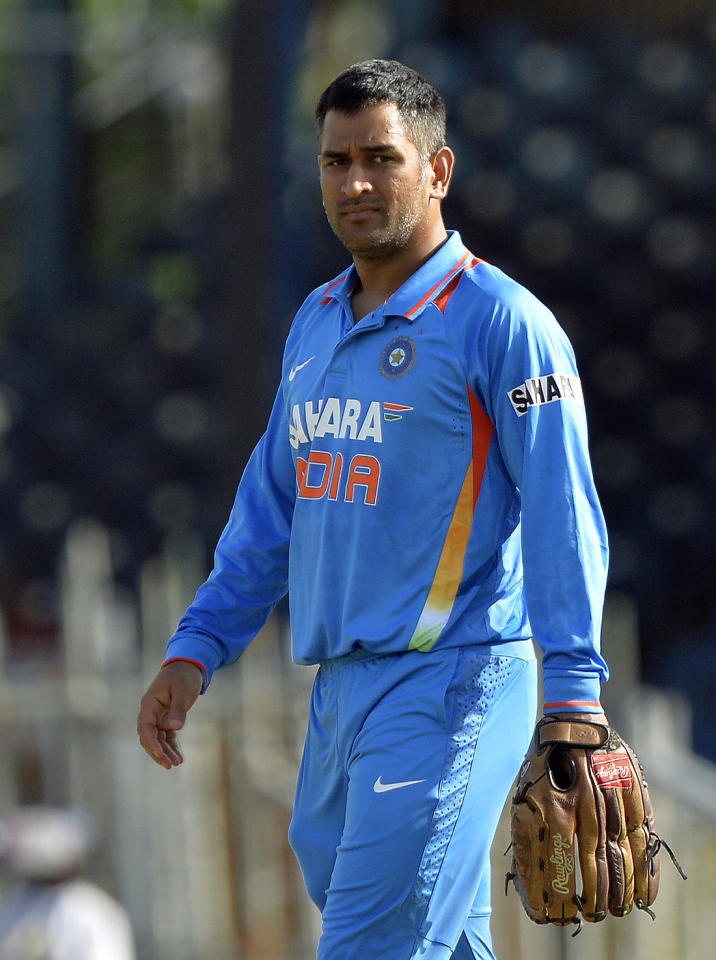 Indian cricket team regular captain Mahendra Sing Dhoni warms up before the start of the second innings during the sixth match of the Tri-Nation series between India and Sri Lanka at the Queen's Park Oval stadium in Port of Spain on July 9, 2013. Dhoni, who injured his hamstring during India's first match of the series, could play in the tournament's final if India make the top two, according to stand-in captain Virat Kohli. AFP PHOTO/Jewel Samad
