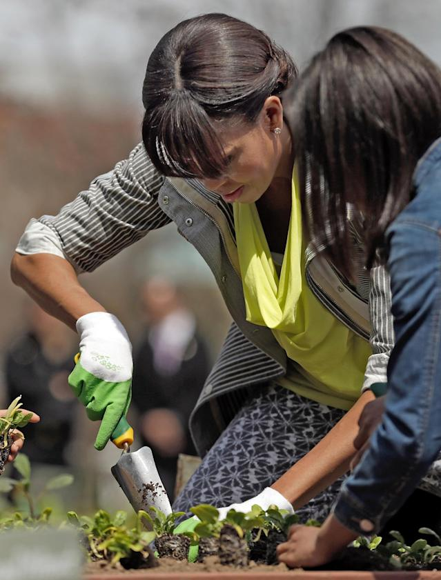"WASHINGTON, DC - APRIL 04: U.S. first lady Michelle Obama plants the White House Kitchen Garden on the South Lawn of the White House April 4, 2013 in Washington, DC. For the fifth time, the first lady invited students from ""schools that have made exceptional improvements to school lunches"" from Florida, Massachusetts, Tennessee and Vermont to help her plant the garden. (Photo by Win McNamee/Getty Images)"