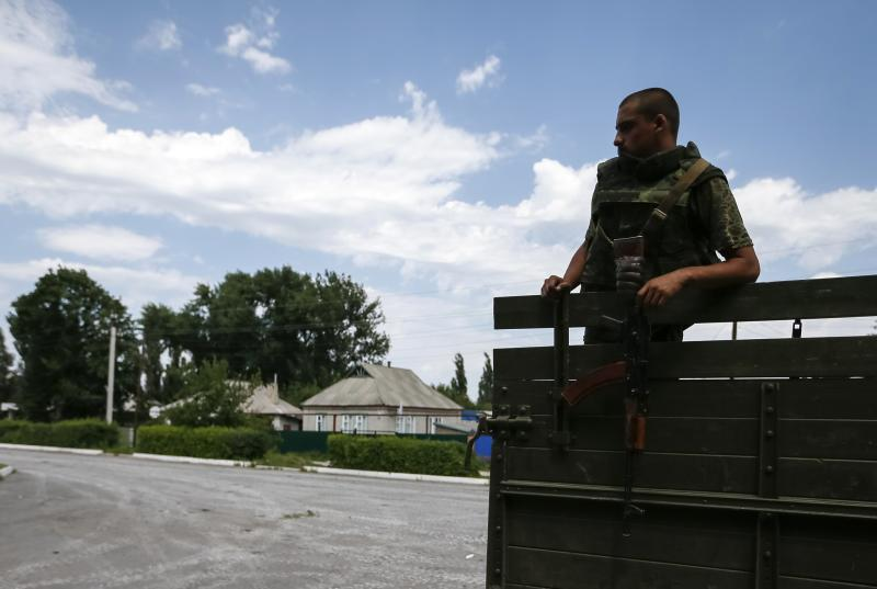 """A Ukrainian soldier stands guard in the eastern Ukrainian town of Seversk July 12, 2014. Ukrainian war planes bombarded separatists along a broad front on Saturday, inflicting huge losses, Kiev said, after President Petro Poroshenko said """"scores and hundreds"""" would be made to pay for a deadly missile attack on Ukrainian forces. REUTERS/Gleb Garanich (UKRAINE - Tags: POLITICS CIVIL UNREST MILITARY)"""