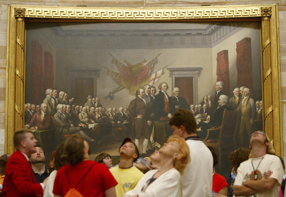 """FILE - In this Thursday, May 15, 2003 file photo, visitors tour the Capitol Rotunda near John Trumbull's painting titled """"Declaration of Independence, July 4th, 1776"""". On that day, the Continental Congress formally endorsed the Declaration of Independence. Celebrations began within days: parades and public readings, bonfires and candles and the firing of 13 musket rounds, one for each of the original states. Nearly a century passed before the country officially named its founding a holiday. (AP Photo/Charles Dharapak)"""