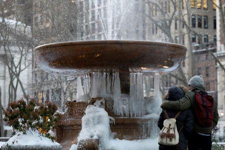 A couple embraces in front of an ice-covered fountain in Bryant Park in New York