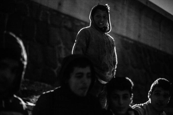 A group of Moroccan kids sit on the breakwater at Melilla's harbor in 2014. (Photo: José Colón/MeMo for Yahoo News)