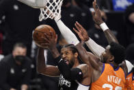 Los Angeles Clippers guard Paul George, left, shoots as Phoenix Suns center Deandre Ayton defends during the second half in Game 3 of the NBA basketball Western Conference Finals Thursday, June 24, 2021, in Los Angeles. (AP Photo/Mark J. Terrill)