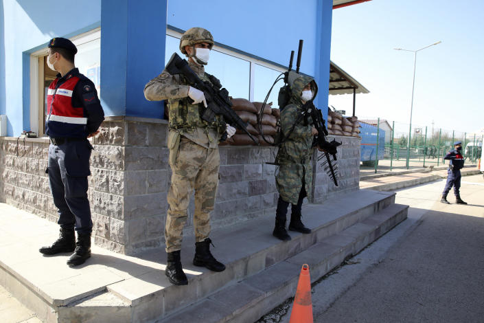 Soldiers stand in guard as people wait outside a courthouse before the trial of 497 defendants, in Sincan, outside the capital Ankara, Turkey, Wednesday, April 7, 2021. The court was expected to deliver a verdict in their trial for involvement in a failed coup attempt in 2026. The court was expected to deliver a verdict in their trial for involvement in a failed coup attempt in 2026. (AP Photo/Burhan Ozbilici)