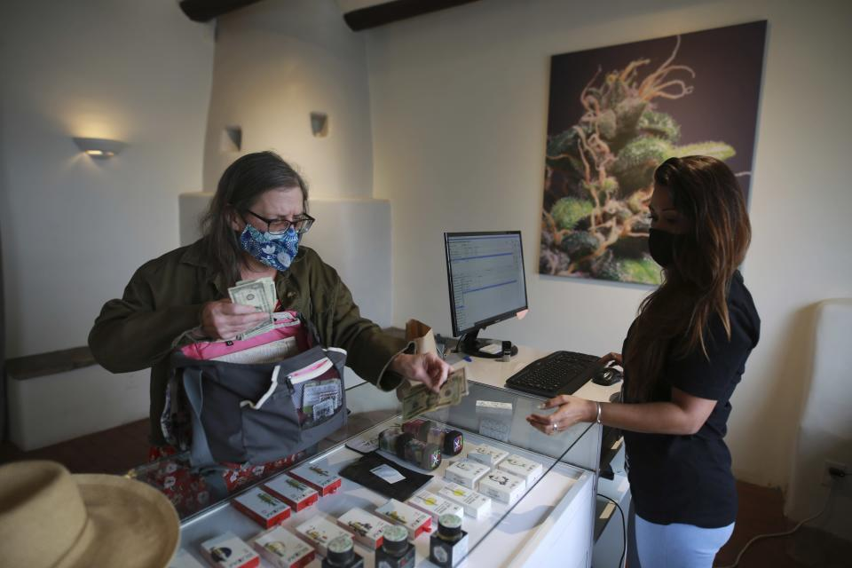 Multiple sclerosis patient and medical marijuana advocate Aurore Bleck buys cannabis at the Minerva medical dispensary on Tuesday, June 29, 2021, in Santa Fe, New Mexico. Marijuana is now legal in New Mexico for recreational use. Black welcomes the legalization legislation, which expands the number of marijuana plants she is allowed to grow. (AP Photo/Cedar Attanasio)