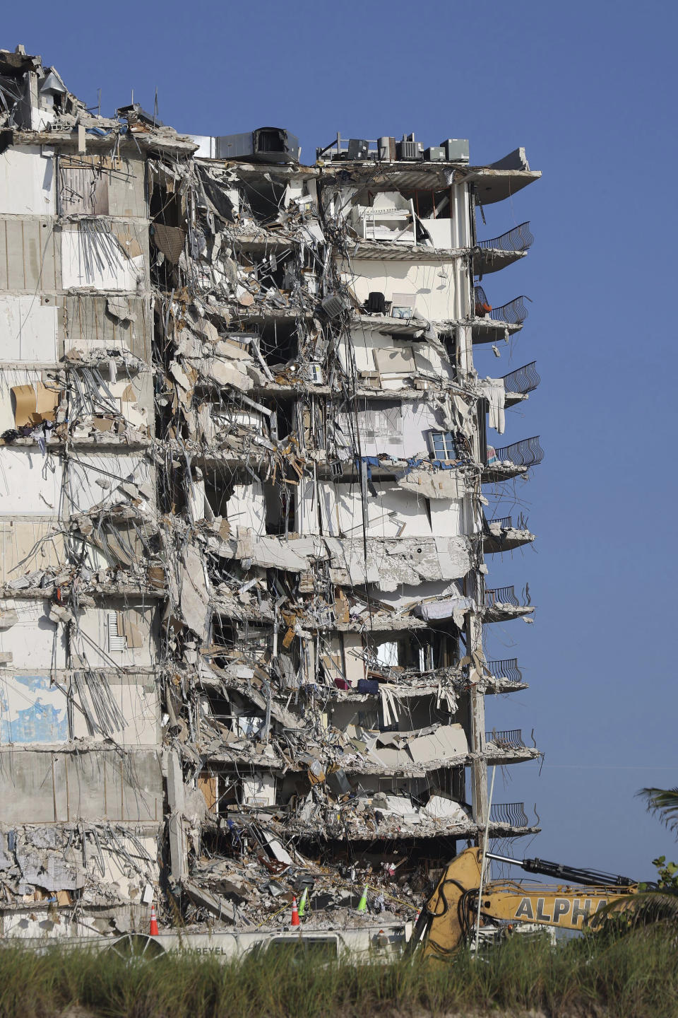 The remaining debris of the collapsed Champlain Towers South during recovery is seen as the operation has slowed down as Miami-Dade Police placed a perimeter about a block south and two blocks north restricting any foot traffic near the site on Sunday, July 4, 2021, in Surfside, Fla. Demolition specialists carefully bored holes to insert explosive charges into the precarious, still-standing portion of a collapsed South Florida condo building that will come down to open up new areas for rescue teams to search. A top Miami-Dade fire official said 80% of the drilling work was complete and the remaining structure could come down as soon as Sunday night. (Carl Juste/Miami Herald via AP)